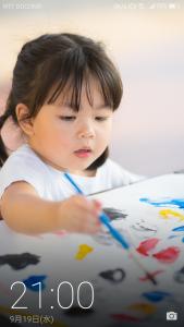 スマホのロック画面に子供の写真が表示されている