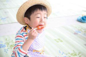 男の子がフランクフルトを食べている写真